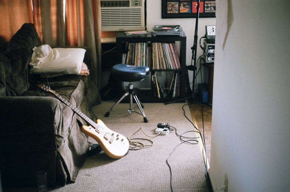 brown electric guitar leaning on sofa