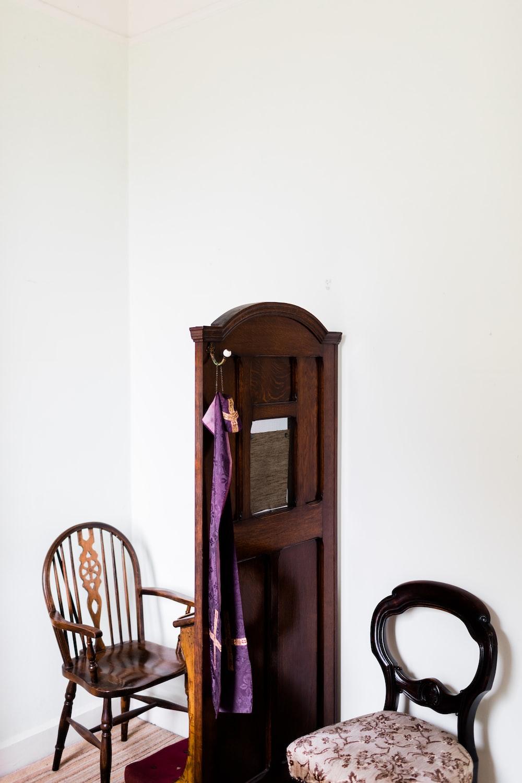 brown wooden cabinet beside brown wooden windsor armchair