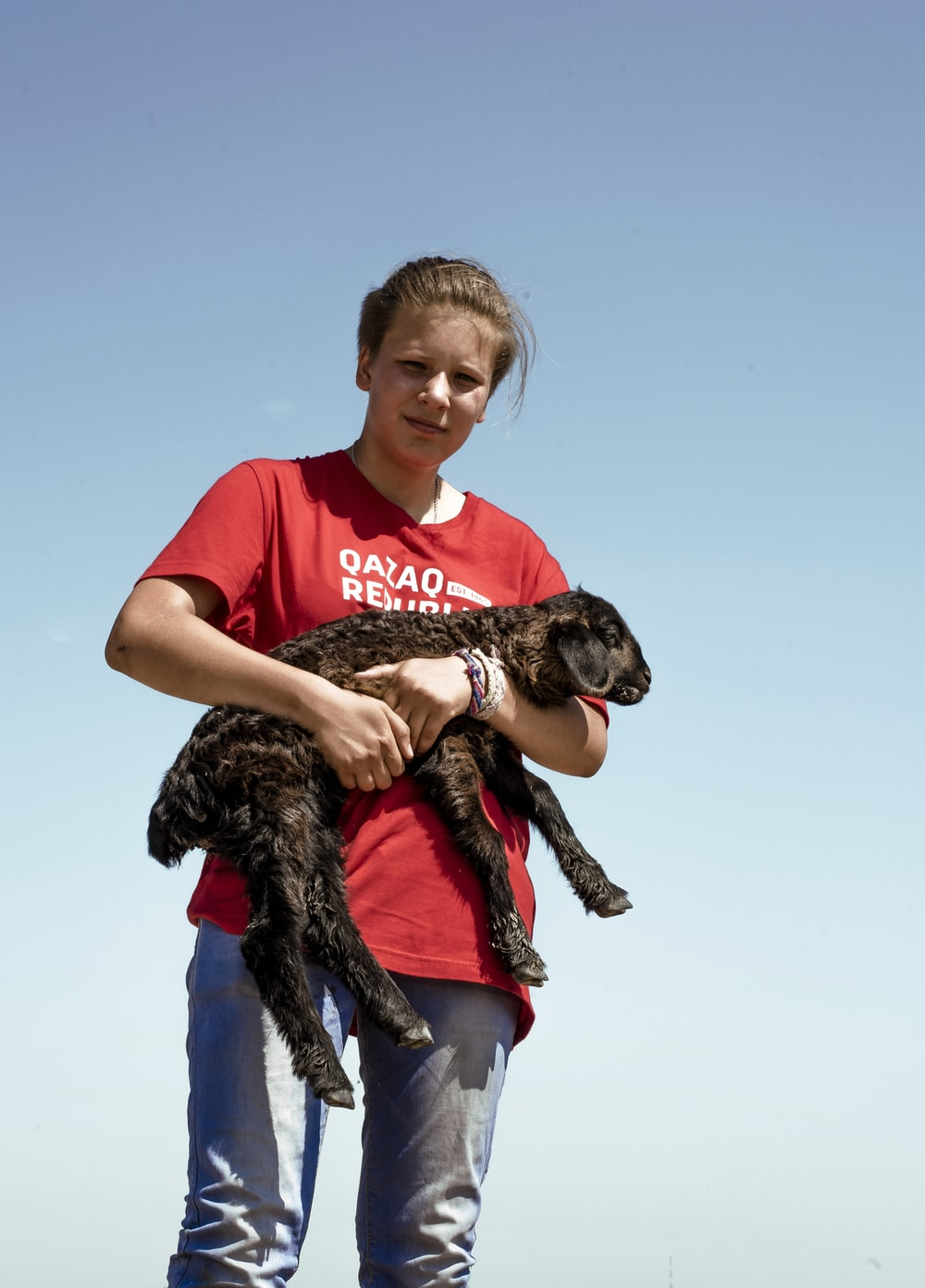 woman carrying goat kid