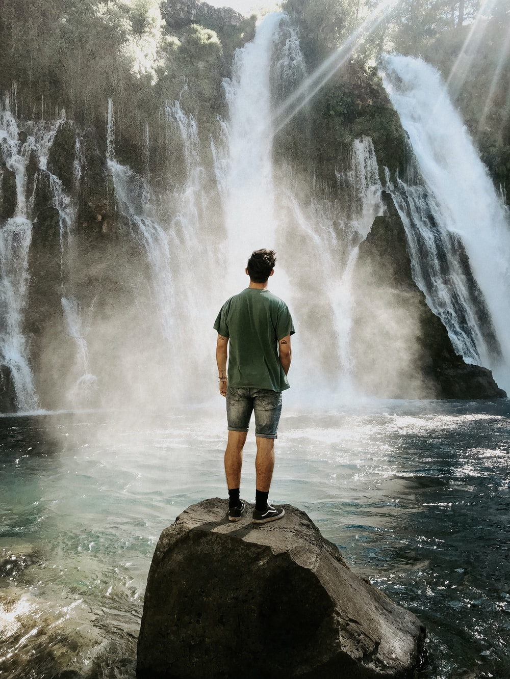 man standing on rock formation facing on waterfalls