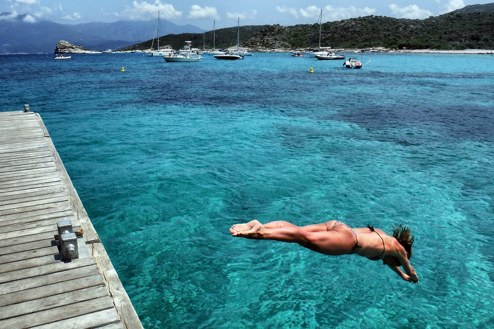 photography of woman diving on body of water