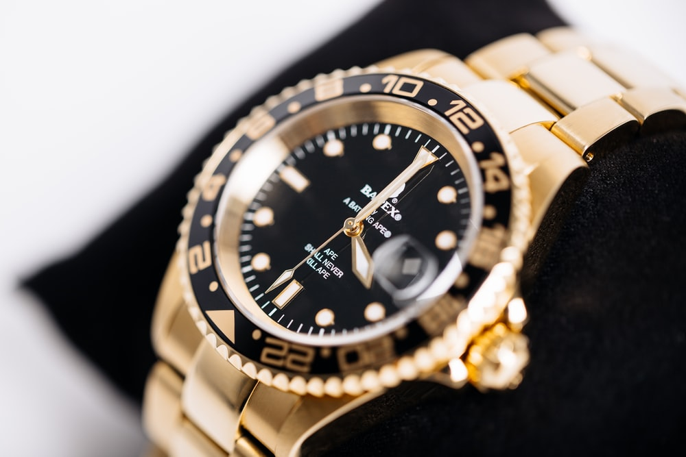 round gold-colored analog watch at 4:00