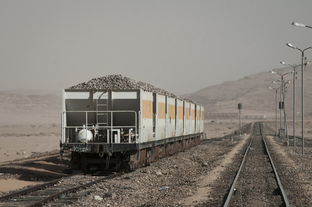 black and gray train carrying gravel