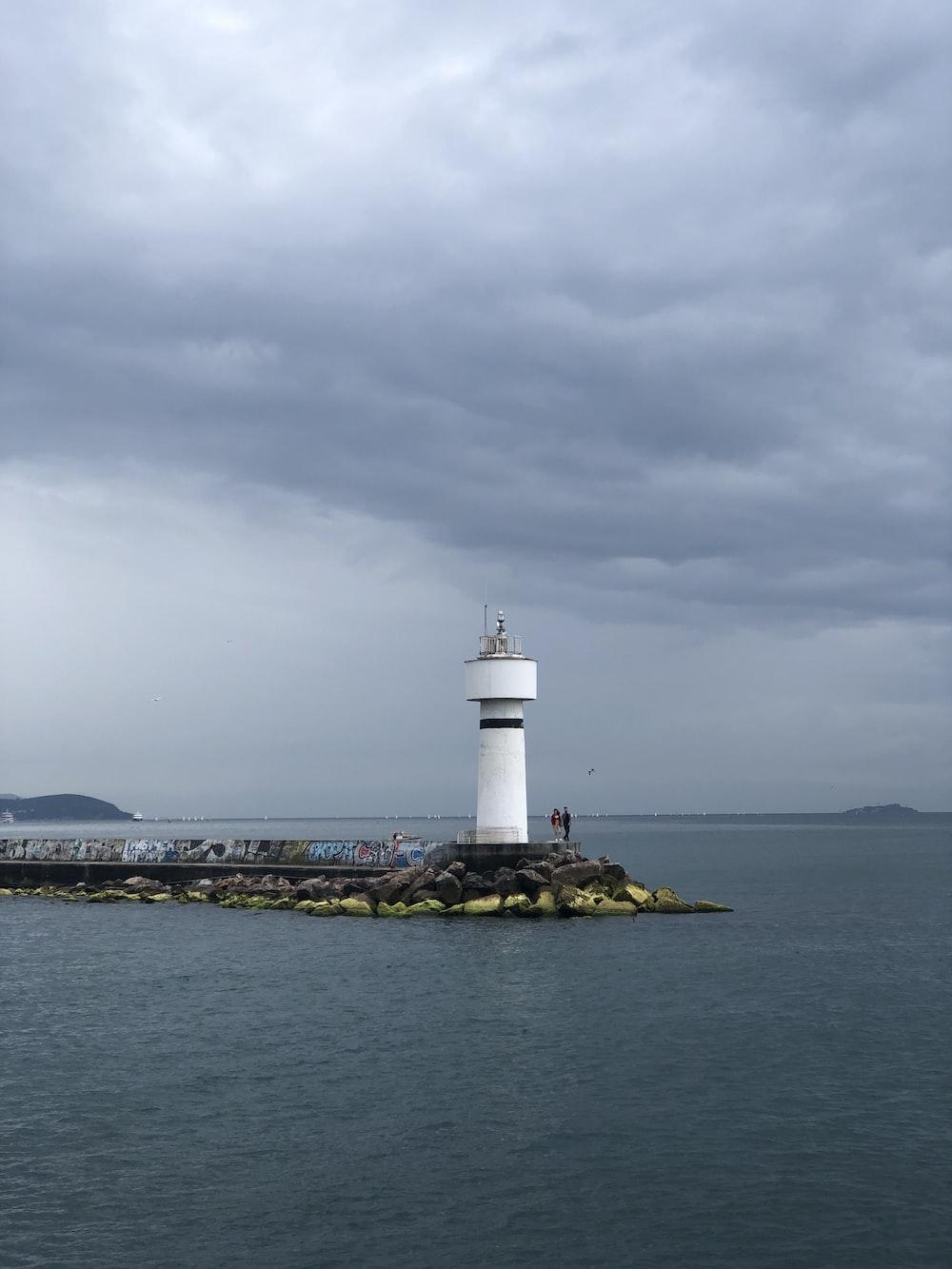 white lighthouse near shore during daytime