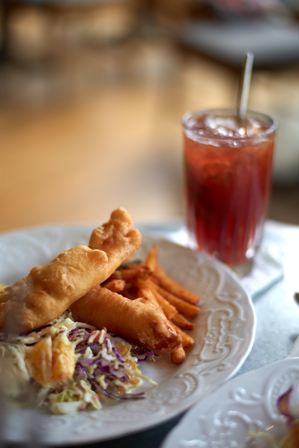 food on round white ceramic plate beside glass of drink