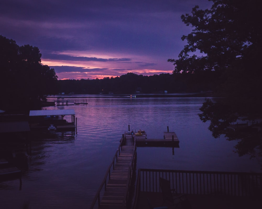 purple sky over lake with wooden dusk at sunset