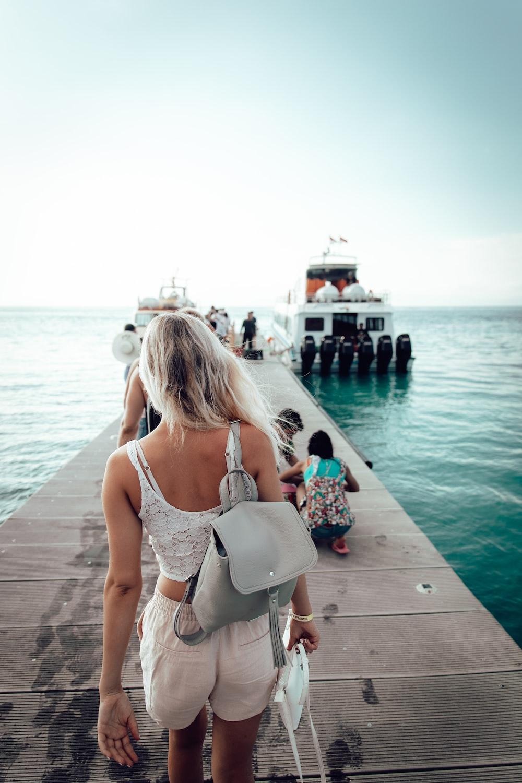 woman walking on dock going on boat