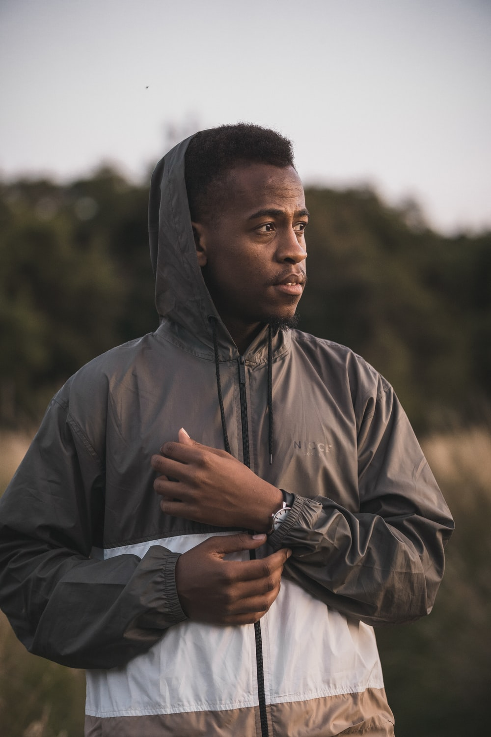 man wearing grey and white zip-up hooded jacket