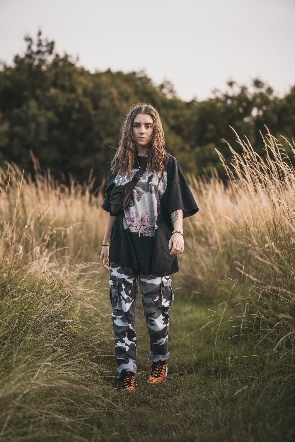 woman in black and grey t-shirt and grey camouflage pants standing in grassy trail
