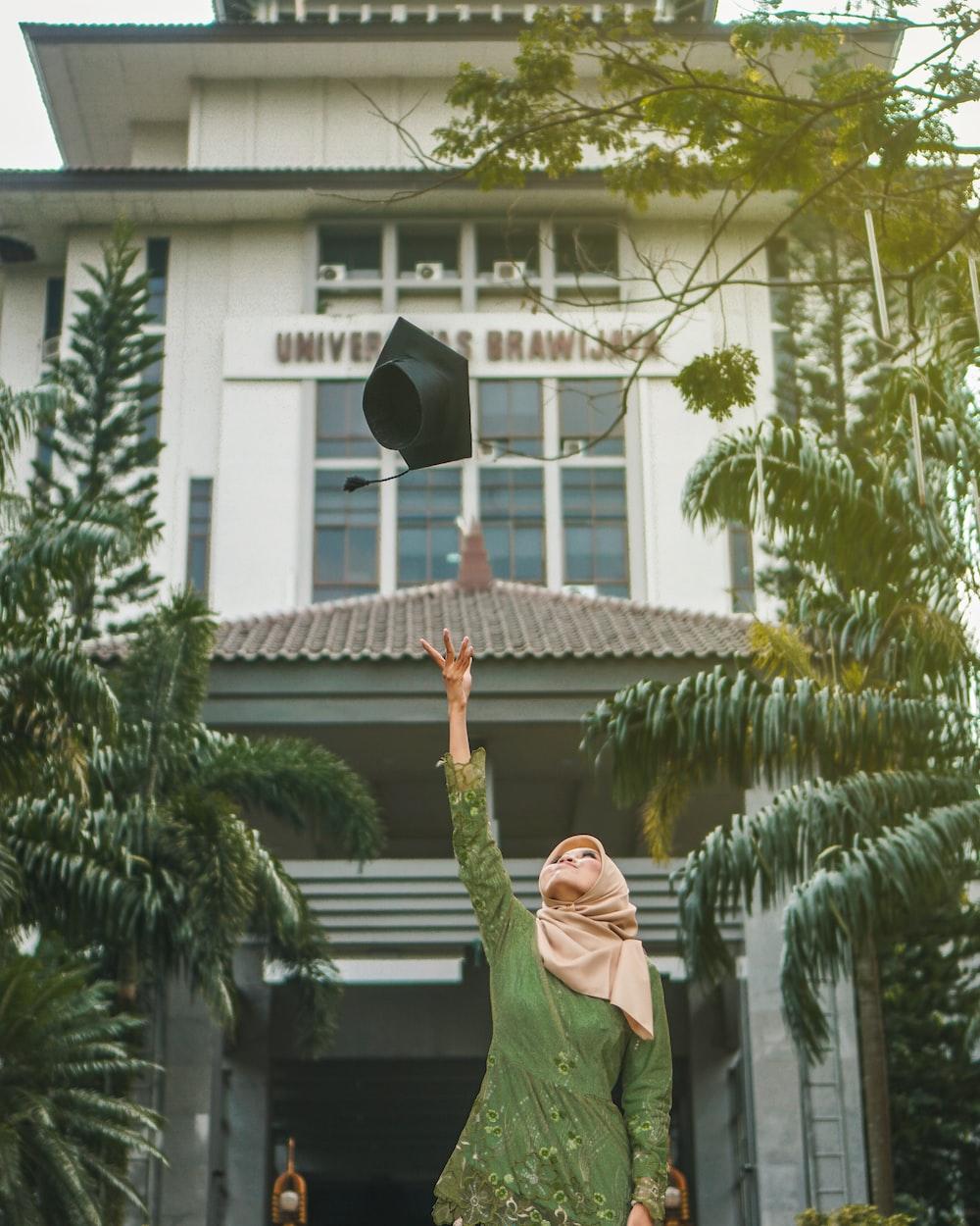 woman throwing mortar board during daytime