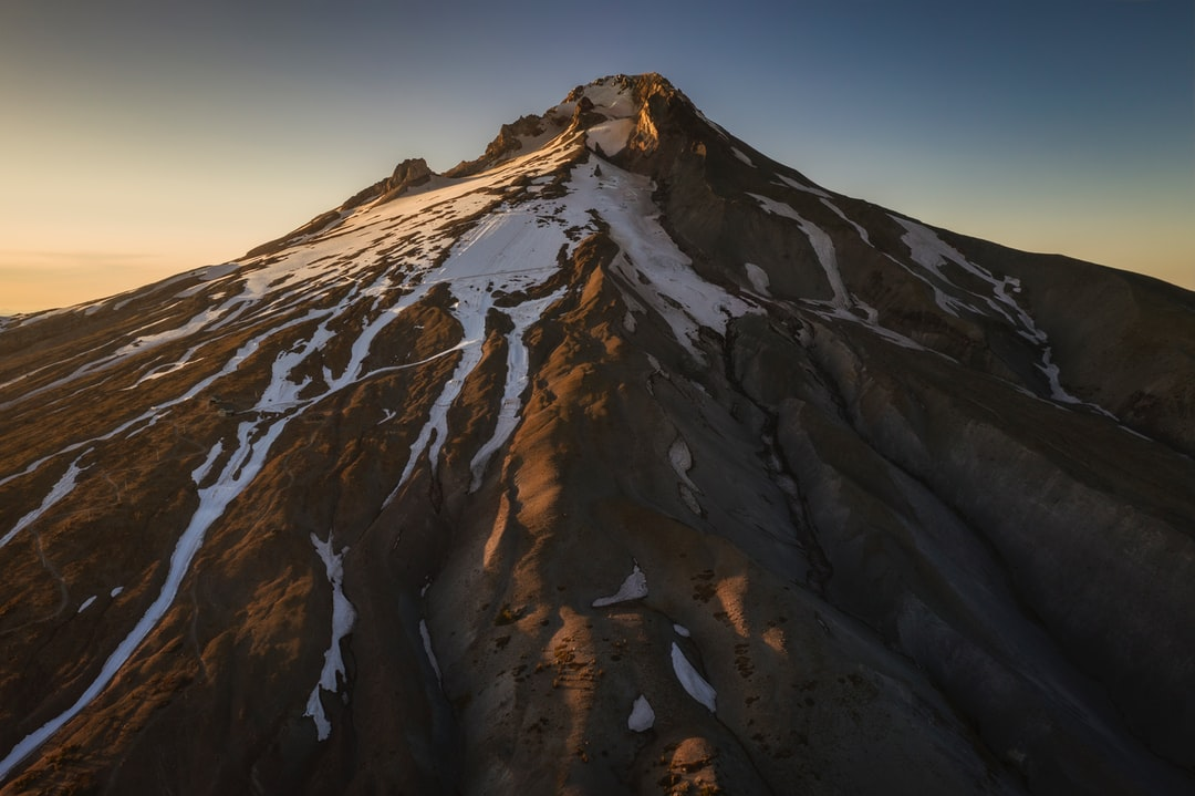 This is the peak of Oregon's Mount Hood, taken at an altitude of about 8,000 feet. On the sunny side, you can see the artificial ski slopes they create during summer. On the right, you can see the remains of this volcano's dying glaciers. The lovely warm colors and shadows are courtesy of clear skies and the setting sun.