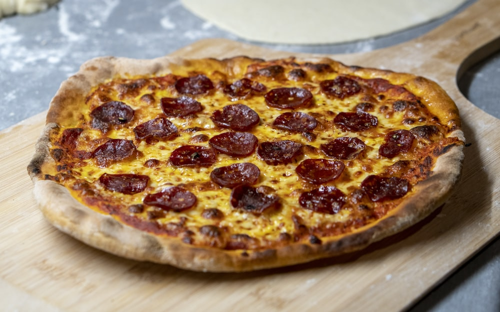 pepperoni pizza on a wooden tray
