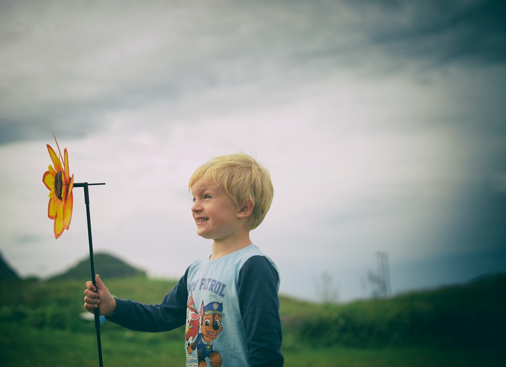 smiling boy holding flower windmill