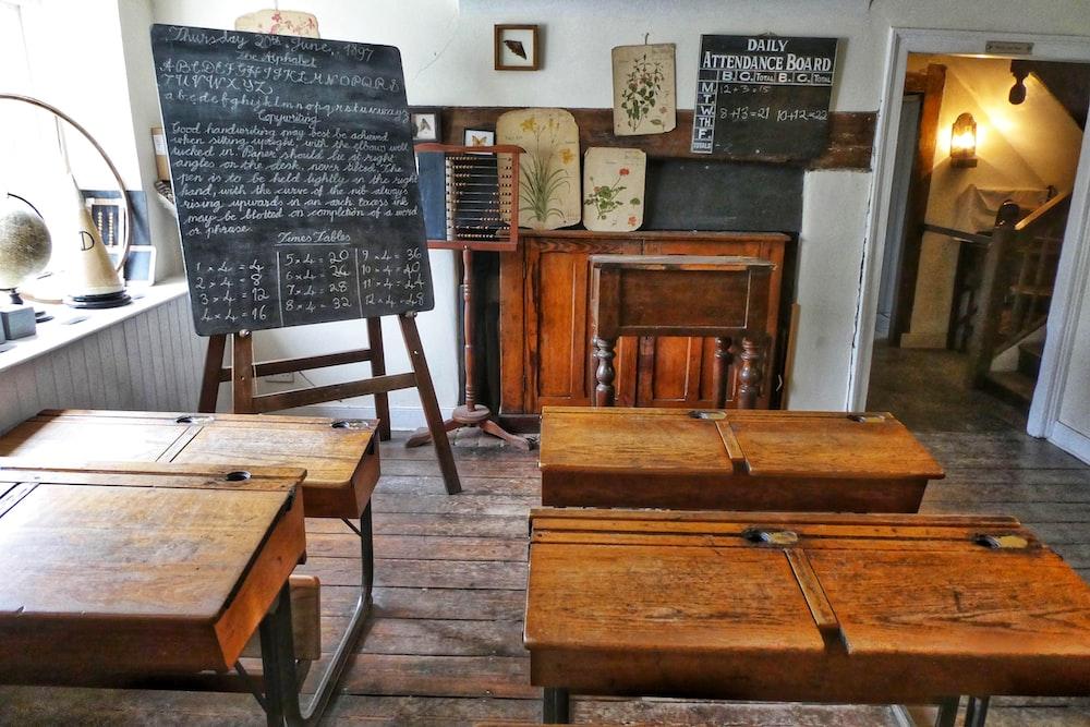 four brown desks inside room