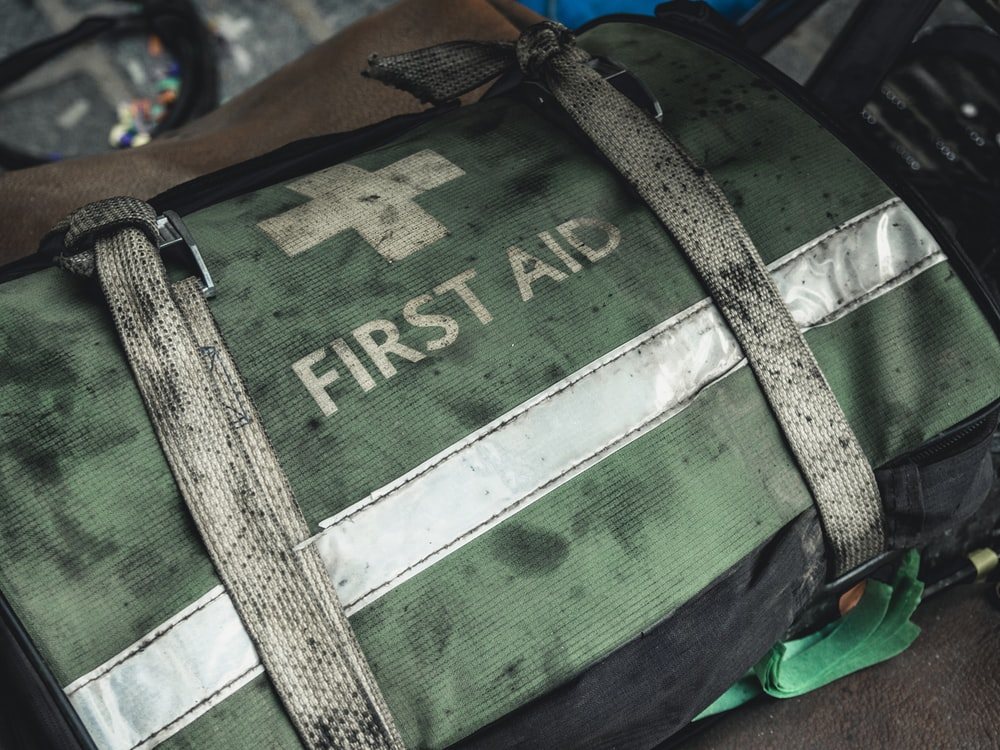 green and black first aid bag