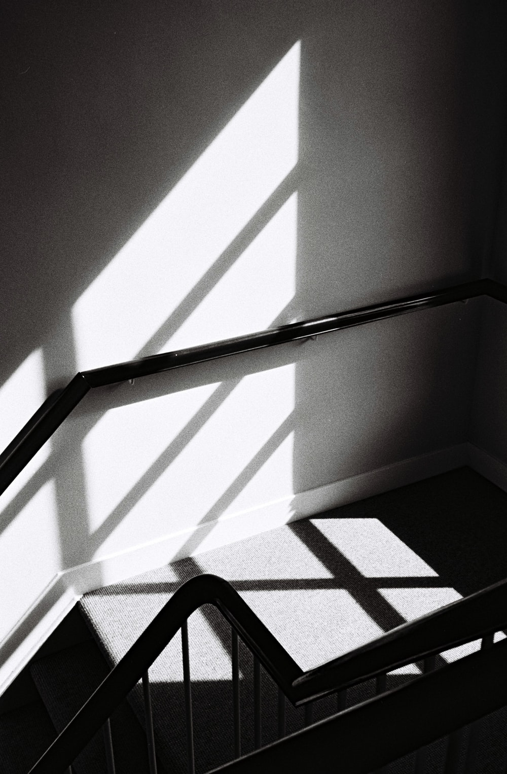 grayscale photo of stairs and handrail