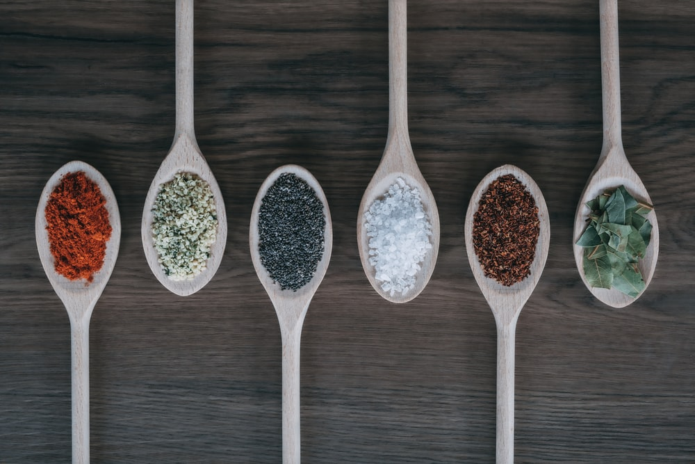 assorted-color spoons with spices
