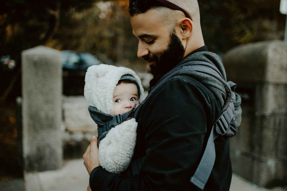 man carrying baby