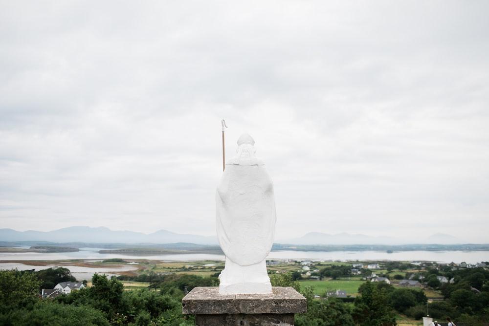 white statue under white clouds