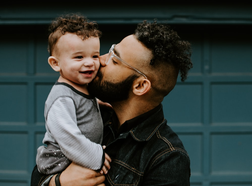 man carrying baby boy and kissing on cheek