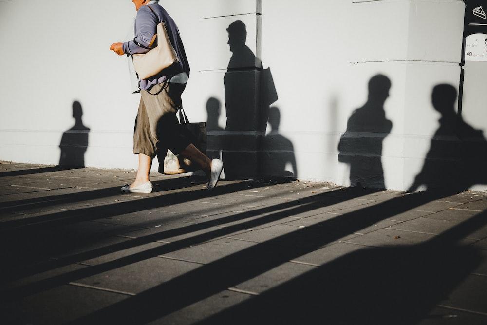 person walking beside wall