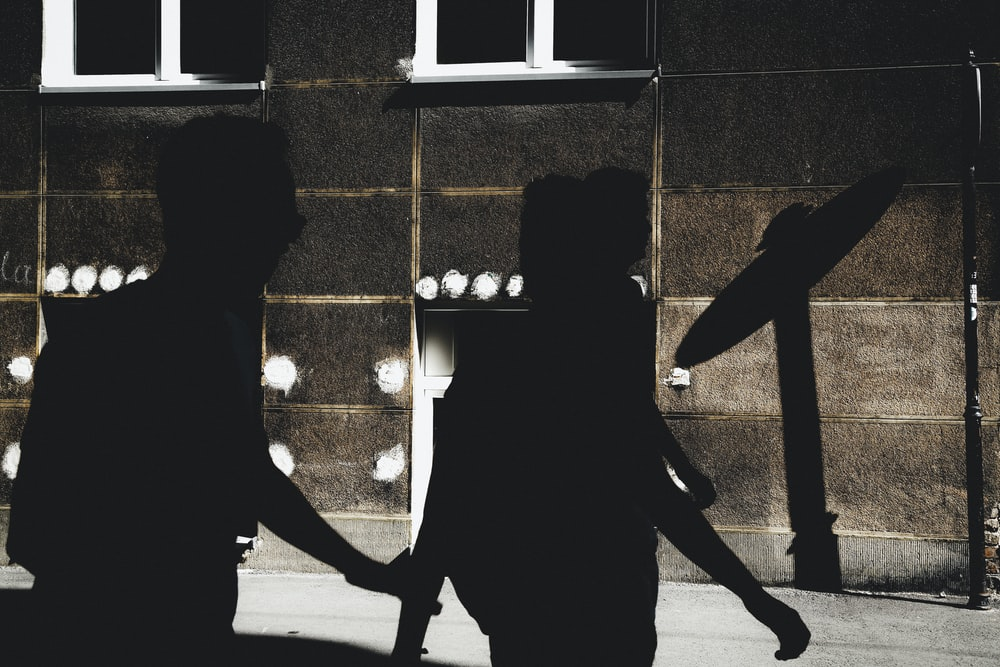 silhouette of three person walking