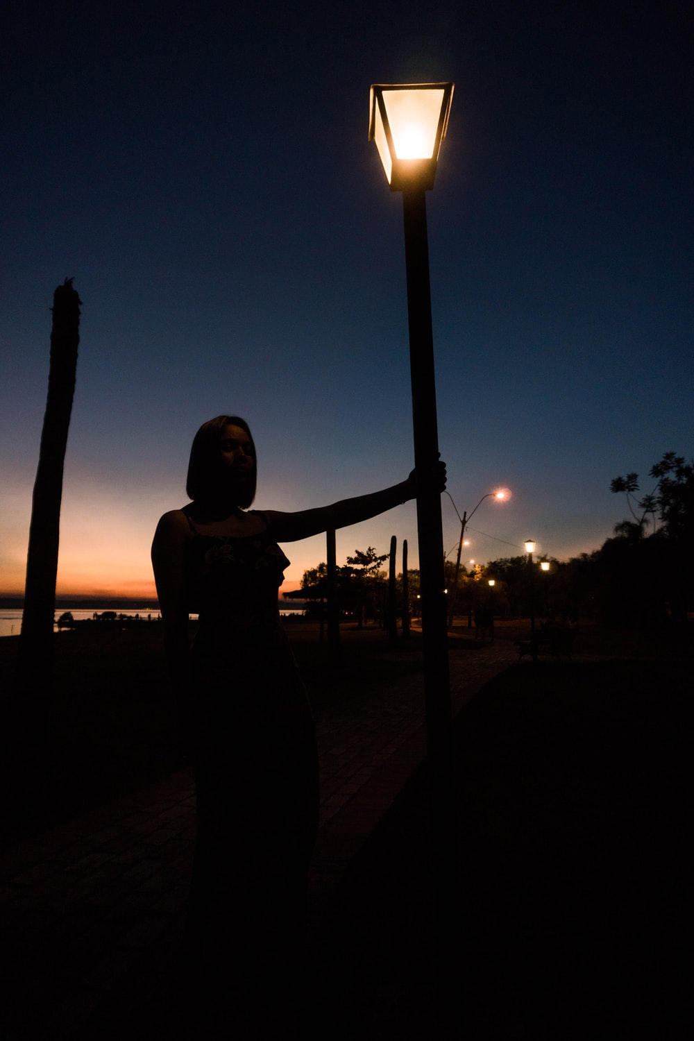 woman holding post lamp during nighttime