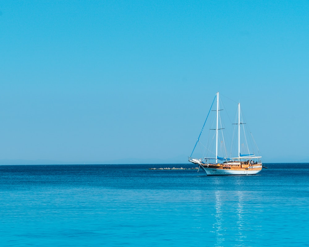 boat on body of water under blue sky at daytime