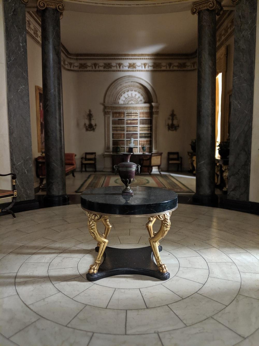 brown vase on round black marble centerpiece table