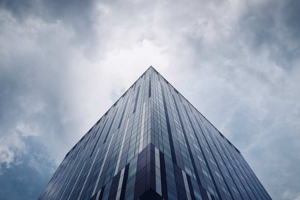 low-angle photo of building under cloudy sky