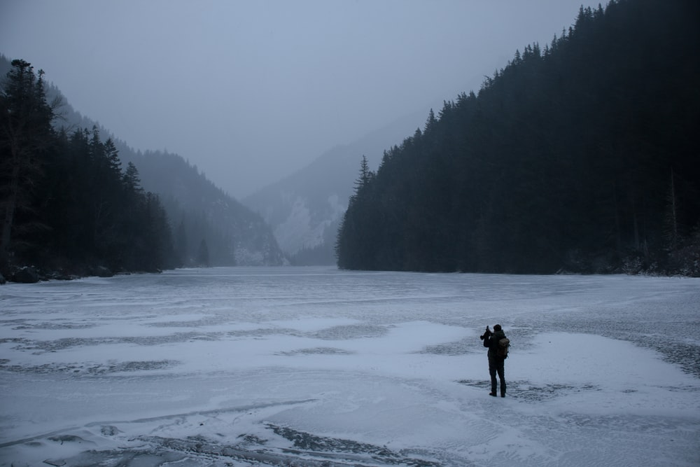 man standing on freezing body of water while facing trees and mountains
