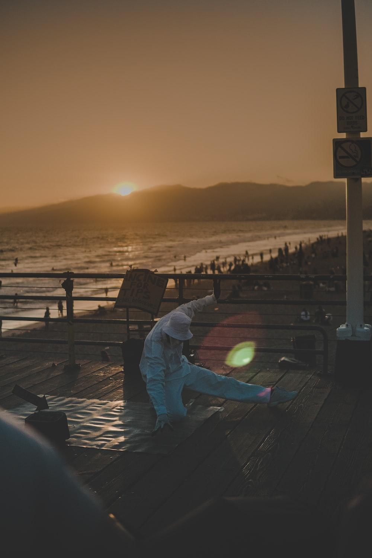 man in white jacket beside sea