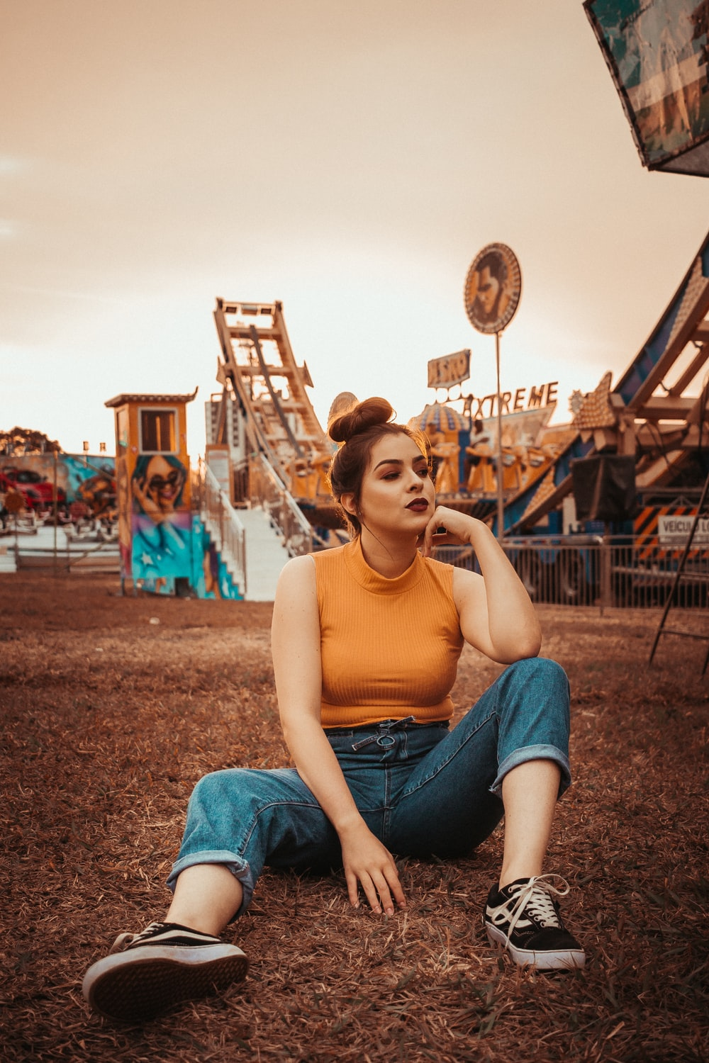 woman sits near carnival ride