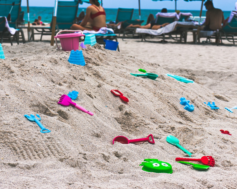 assorted-color toys on sand