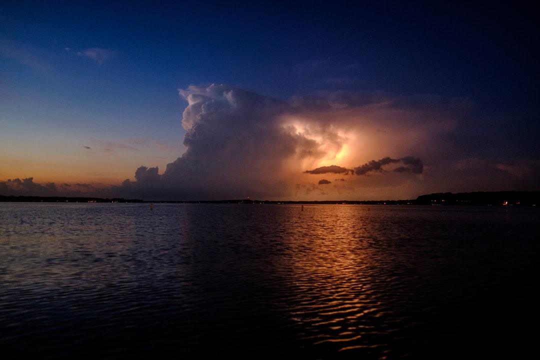 A storm cloud reflecting on the water as it lights up with lightening from within.