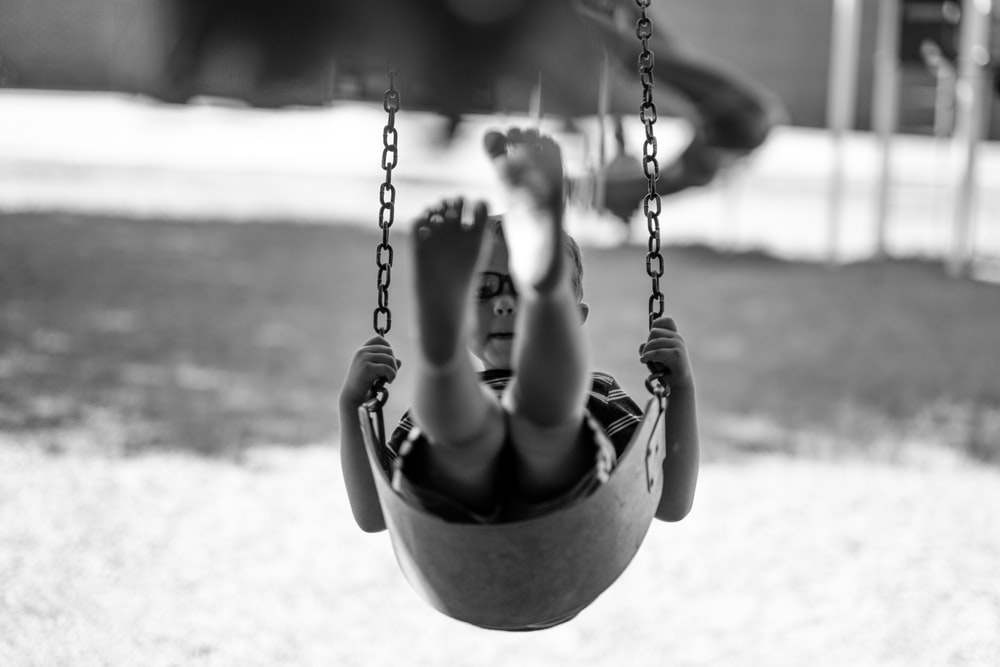 grayscale-photography of boy playing swing chair