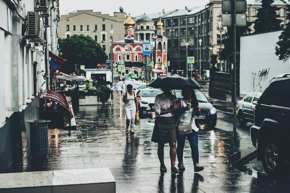 three women with umbrellas walking in sidewalk under rain