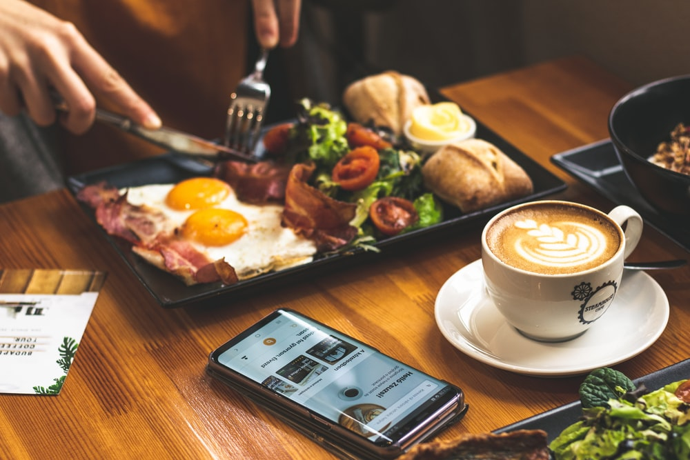 man sitting in front of table with breakfast served