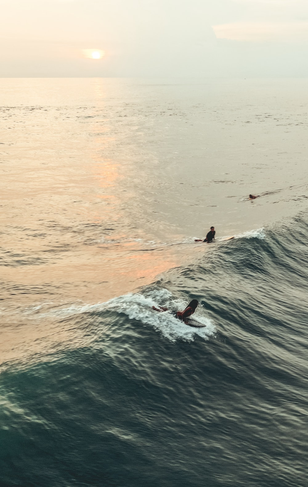person surfing on body of water during golden hour