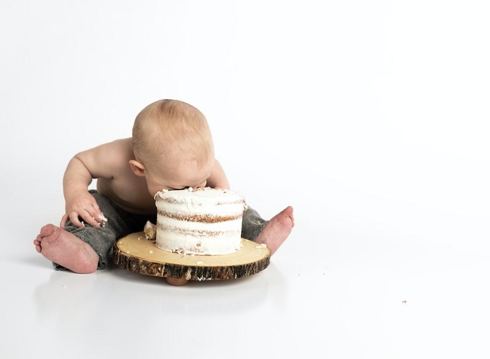 丸いケーキのクローズアップ写真の横に座っている子供