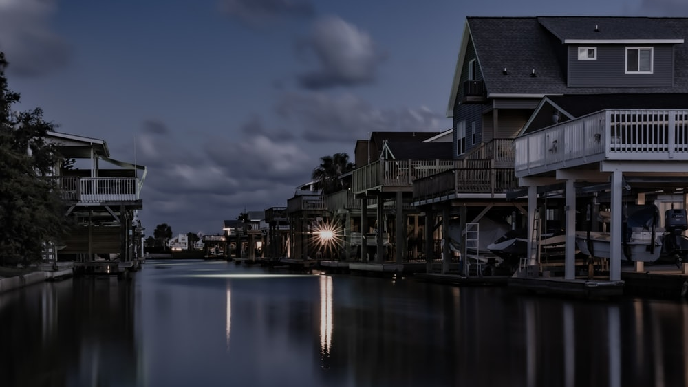 photography of river between buildings during nighttime