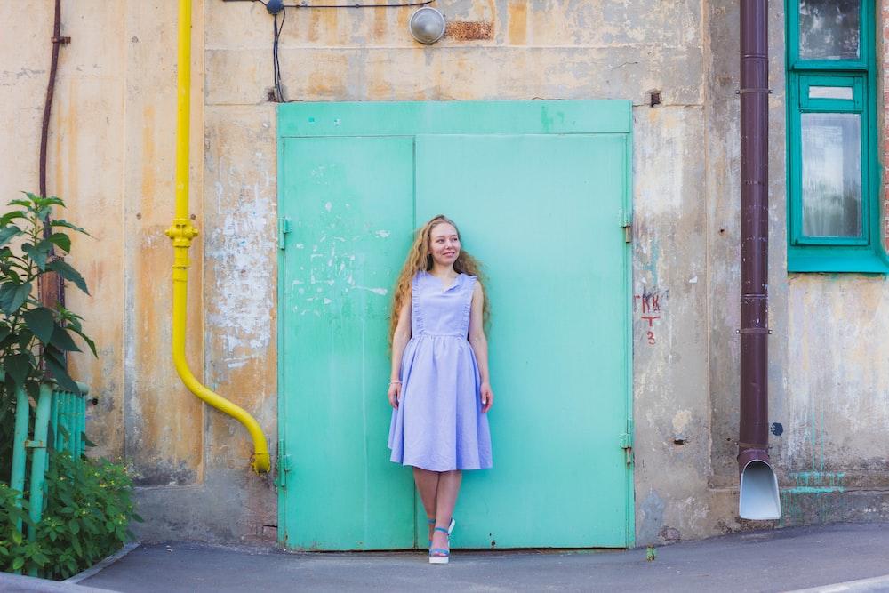 woman standing against teal door