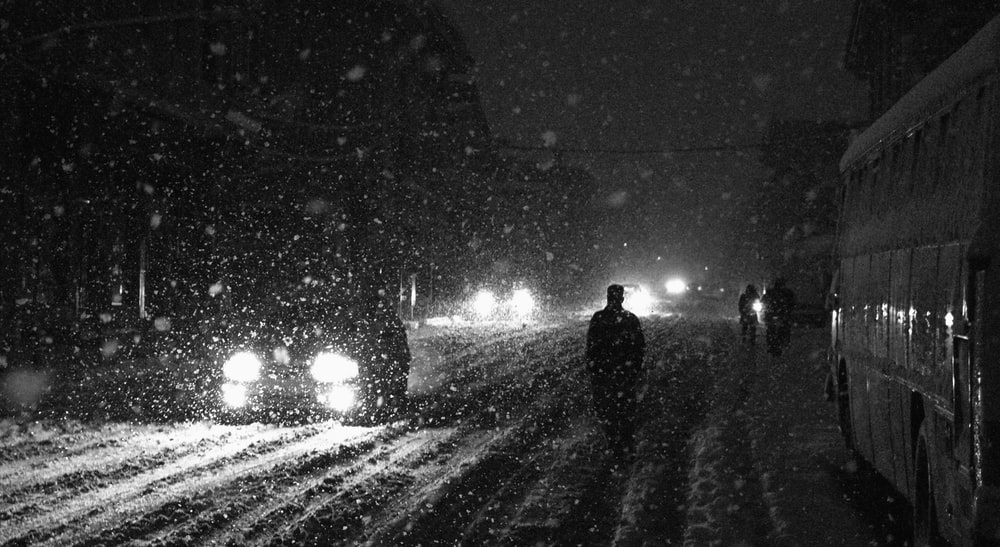 people and vehicles on road during snowstorm
