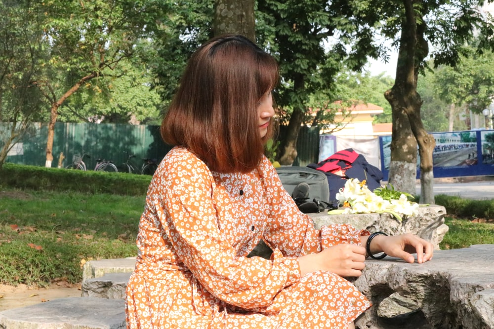 昼間にテーブルと木の近くの岩に座っている女性