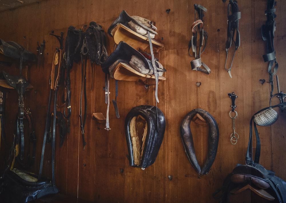 brown leather saddles on brown wall
