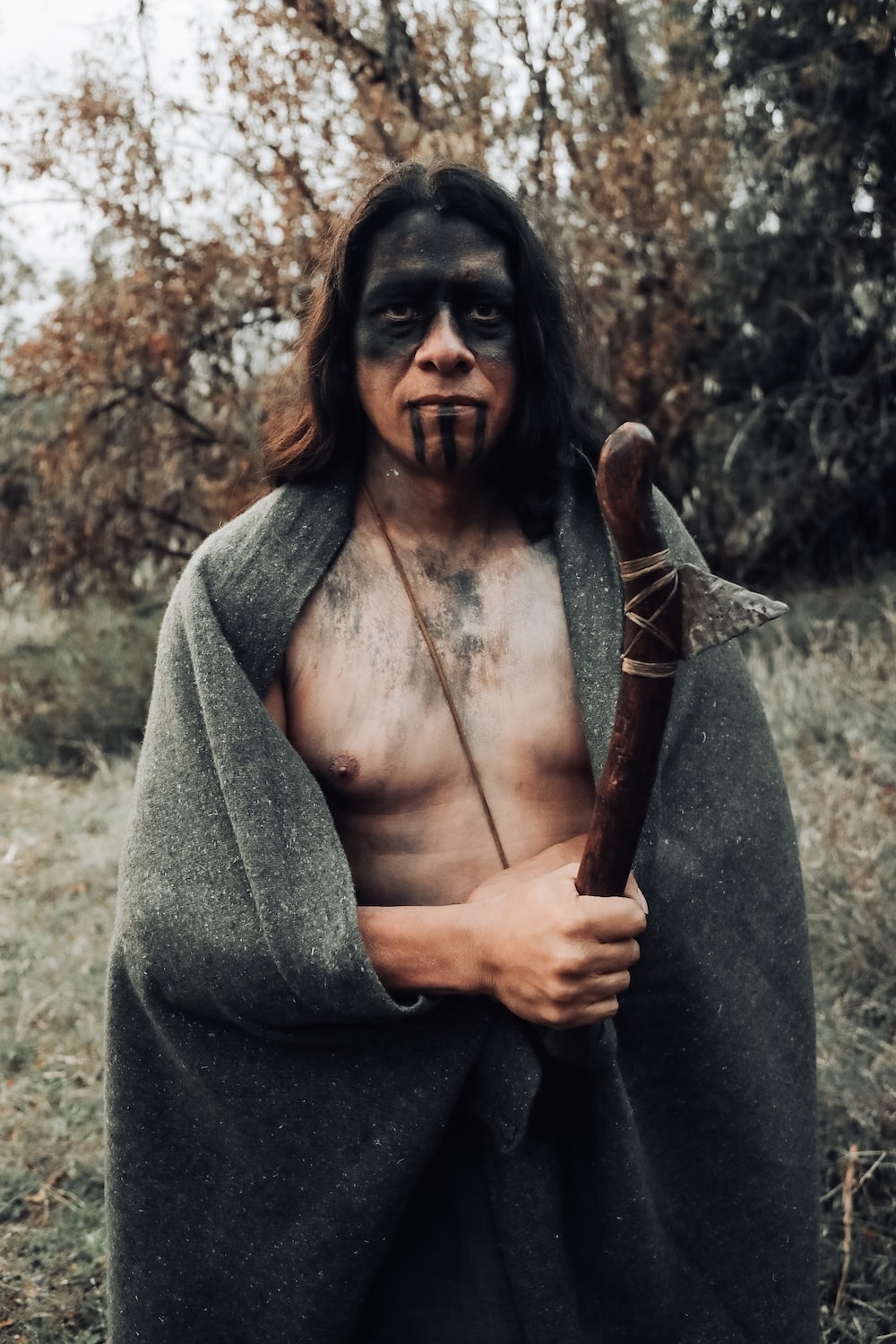 man holding brown wooden staff and gray robe