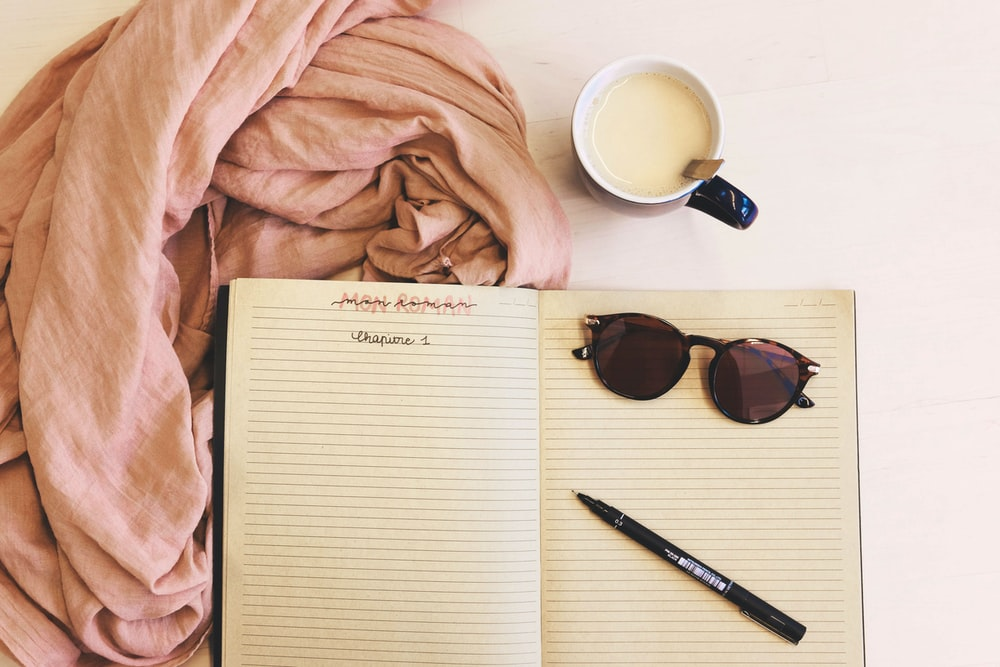 ballpoint pen and sunglasses on opened notebook