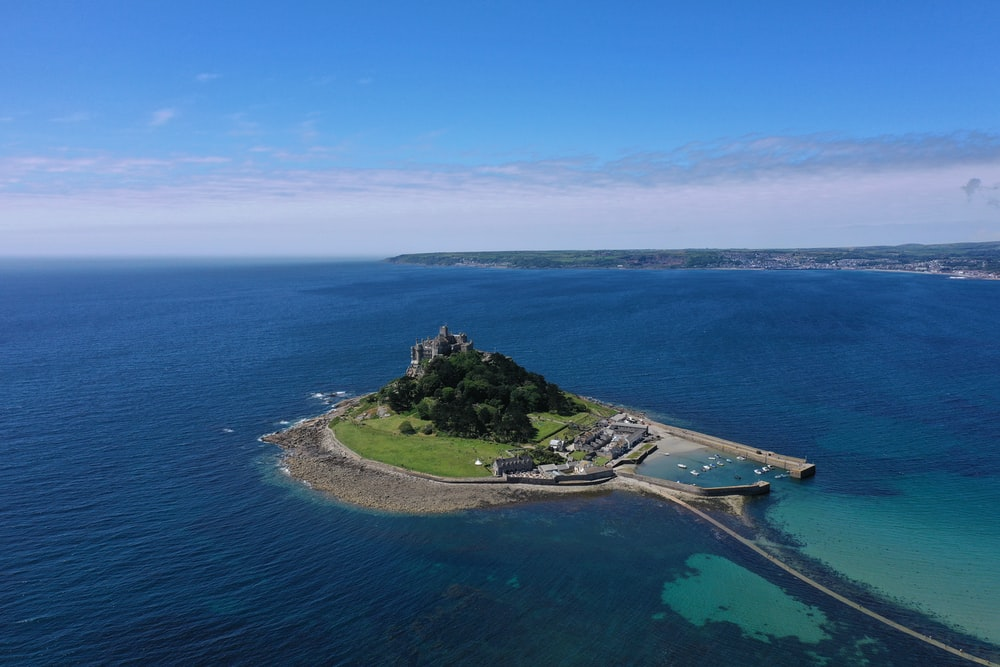green islet during clear blue sky