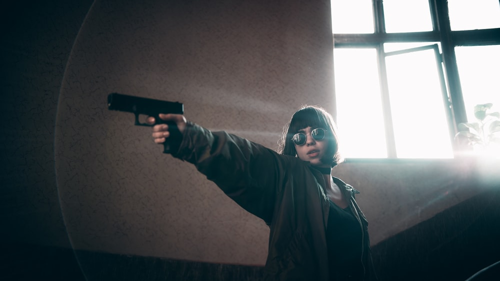 woman aiming gun at her right side