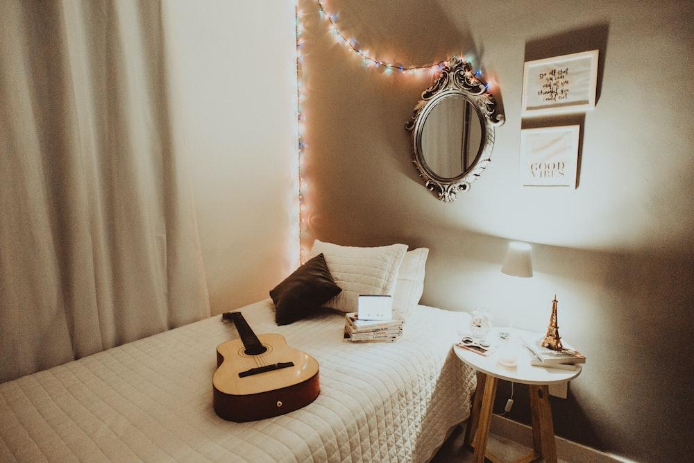 beige guitar on white bedspread